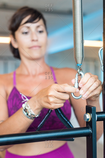 Adult female attaching handle to resistance spring while preparing for Pilates training in gym