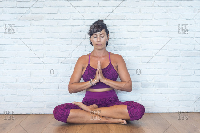 Adult female with closed eyes and clasped hands sitting in Padmasana pose meditating near brick wall during yoga lesson in studio
