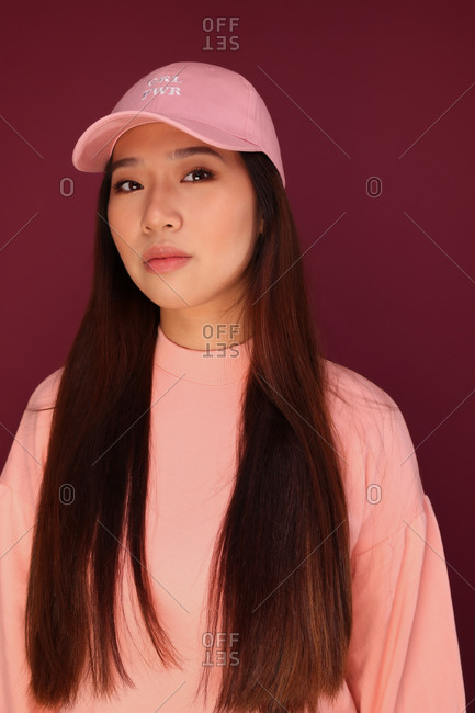 Portrait of young Asian woman in the studio looking at camera. She is wearing pink clothes with serious expression