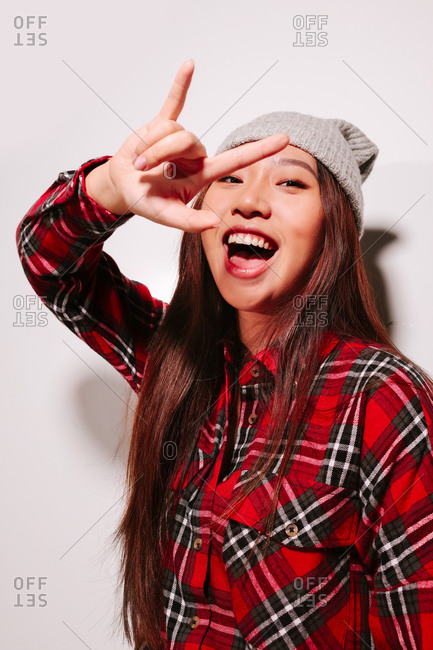 Close-up portrait of cheerful Asian young woman with rock sign