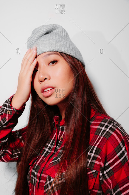 Close-up portrait of cheerful Asian young woman covering her face with her hand