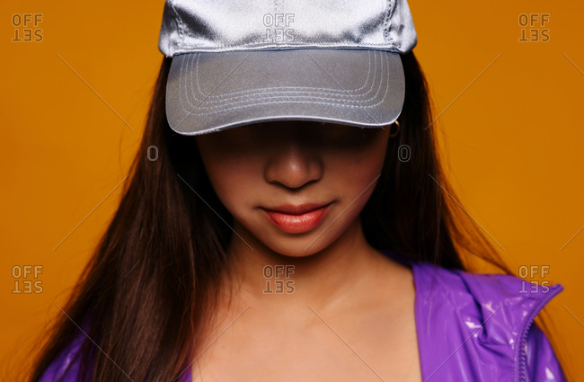 Portrait of Asian young woman. She wears a purple jacket and a grey cap and is looking away smiling against a yellow background