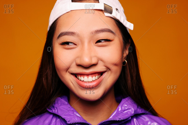 Portrait of happy Asian young woman. She wears a purple jacket and a grey cap and is looking away smiling against a yellow background