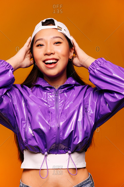 Portrait of happy Asian young woman. She wears a purple jacket and a grey cap and is looking at camera smiling against a yellow background