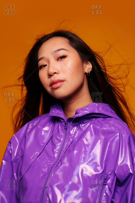 Portrait of Asian young woman with serious expression. She wears a purple jacket and a gray cap and is looking at the camera against a yellow background
