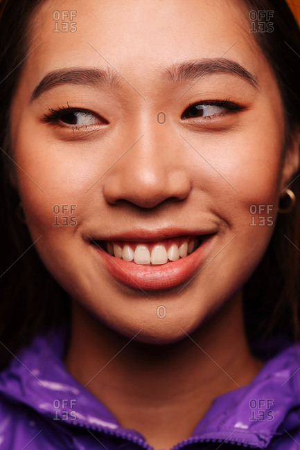 Close-up portrait of cheerful Asian young woman looking aside