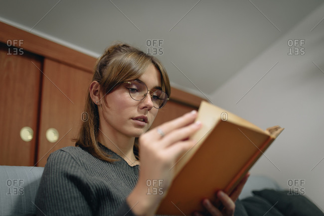 Blonde girl sitting on the bed reading a book