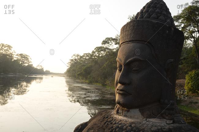 Large stone head caving on a bridge near Angkor Wat