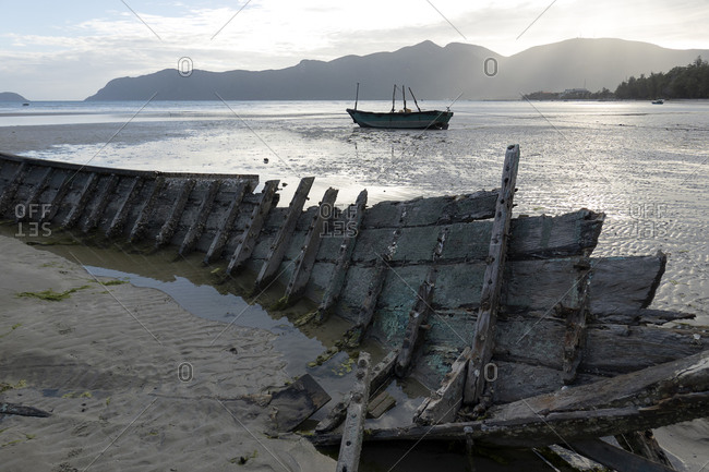Wrecked fishing boat on the beach at low tide in Vietnam