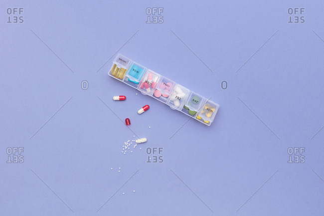 Pills and plastic container for week on colored violet background