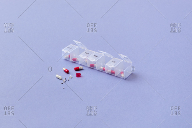 Scattered pills and plastic container for week on colored violet background