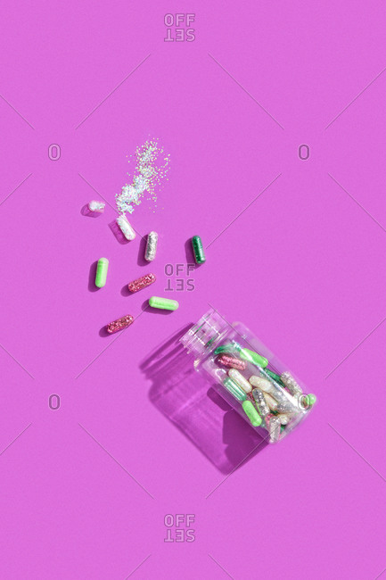 Scattered pills with glitter and plastic container on colored purple background, top view