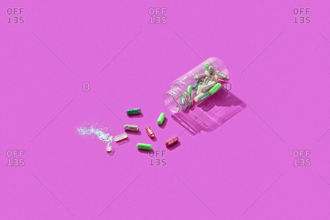 Scattered pills with glitter and plastic container on colored purple background