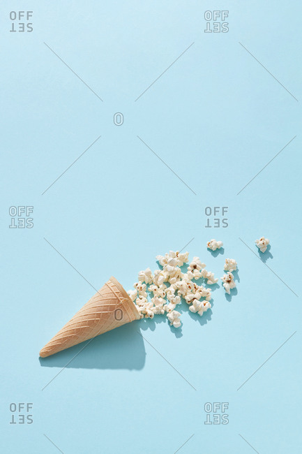 Tasty cooked classic popcorn in cone on blue background, copy space