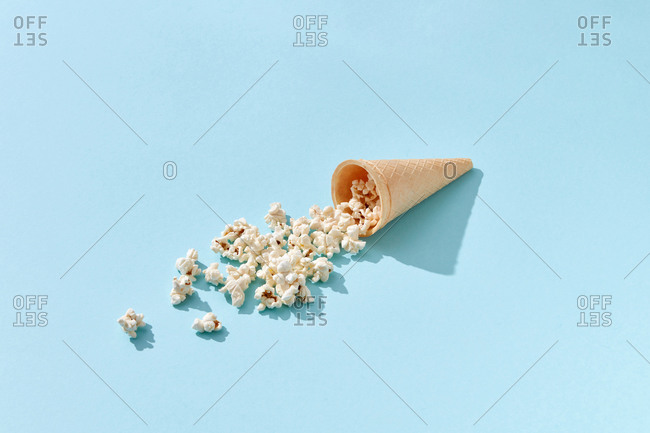 Tasty cooked classic popcorn in cone on blue background