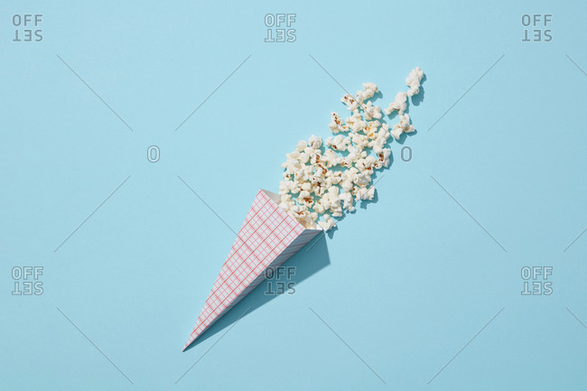 Tasty cooked classic popcorn in paper cone on blue background