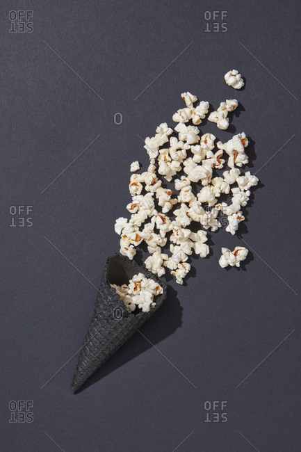 Tasty cooked classic popcorn in black cone on black background