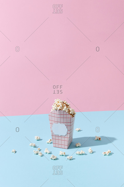 Delicious cooked classic popcorn in carton container on pink and blue background, copy space