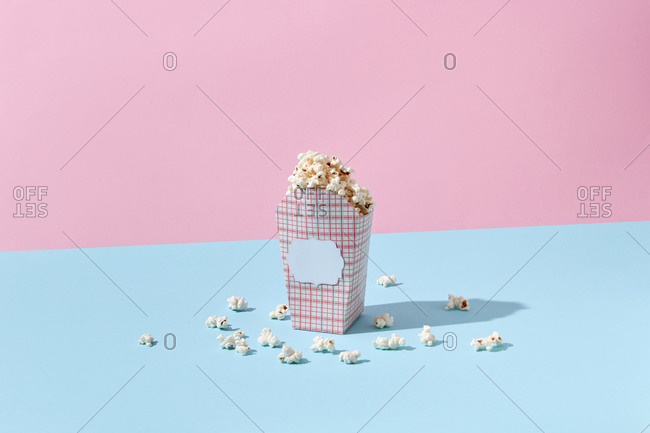 Delicious cooked popcorn in carton container on pink and blue background, copy space