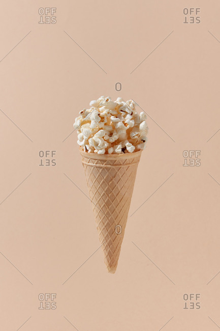 Tasty cooked classic popcorn in cone on beige background