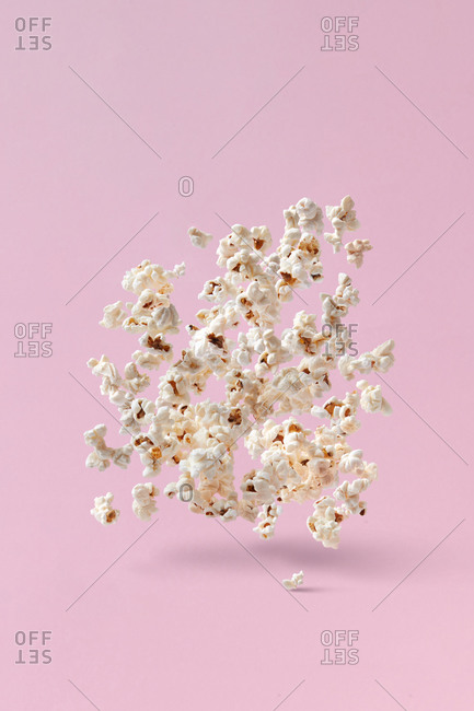 Closeup of appetizing cooked salty falling popcorn on pink background