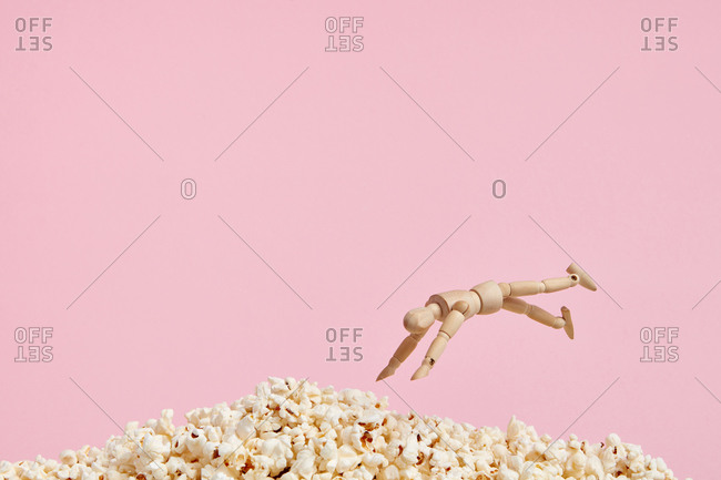 Wooden brown toy in shape of human jumping in cooked appetizing heap of popcorn on pink background
