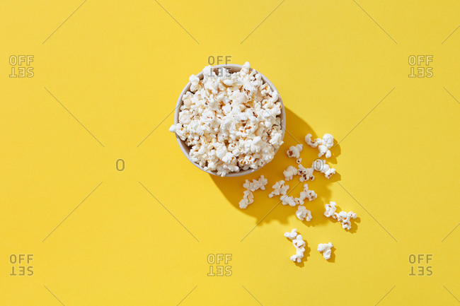 Appetizing cooked popcorn in bowl on bright yellow background, top view