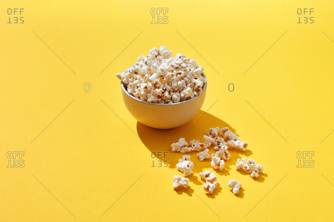 Appetizing cooked popcorn in bowl on bright yellow background