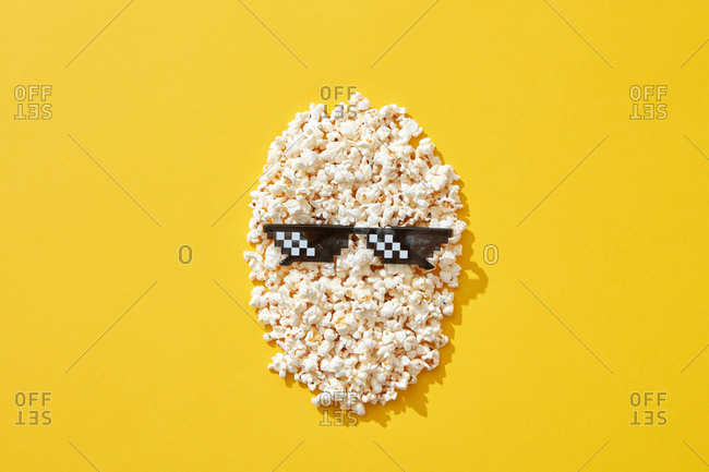 Popcorn face with black cinema glasses on bright yellow background, top view