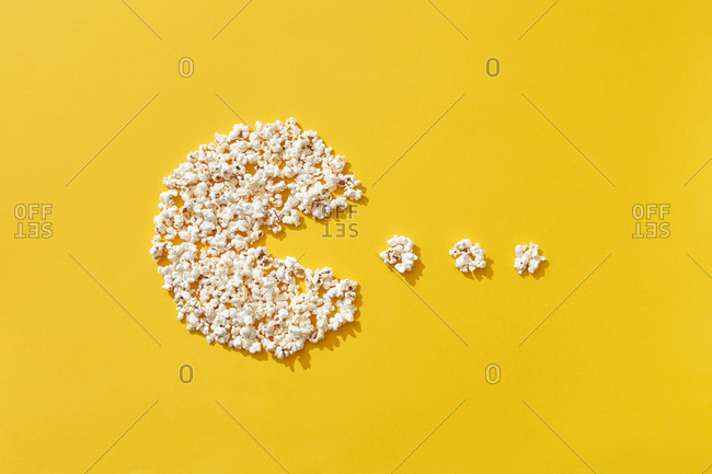 Popcorn sign of fish eating small pieces on bright yellow background, top view