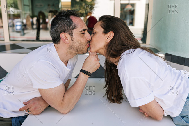 Young loving couple kissing in a coffee shop