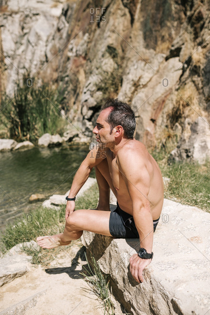 Young man in a bathing suit sitting on a rock in a quarry looking at the water