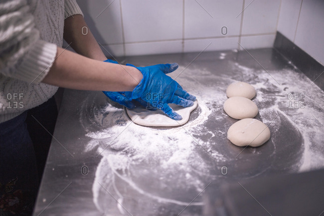 Woman's hands kneading flour with gloves in a kitchen