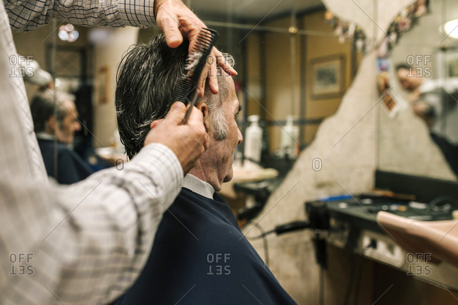 Older man getting his hair cut in a barber shop