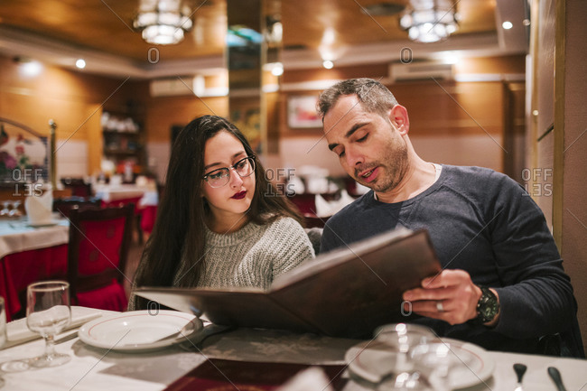 Father and daughter looking at the menu of a Chinese restaurant