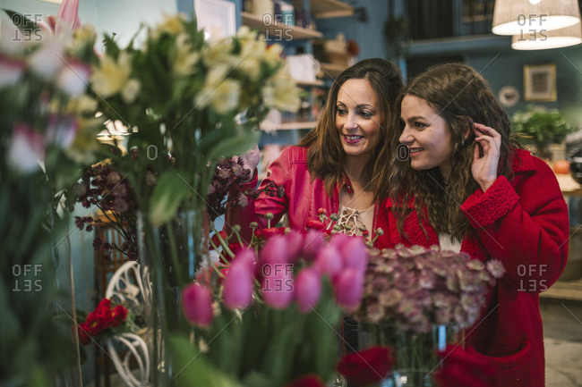 Two young female friends looking at flowers in a florist