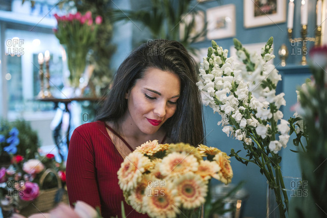 Young woman looking at flowers in a florist