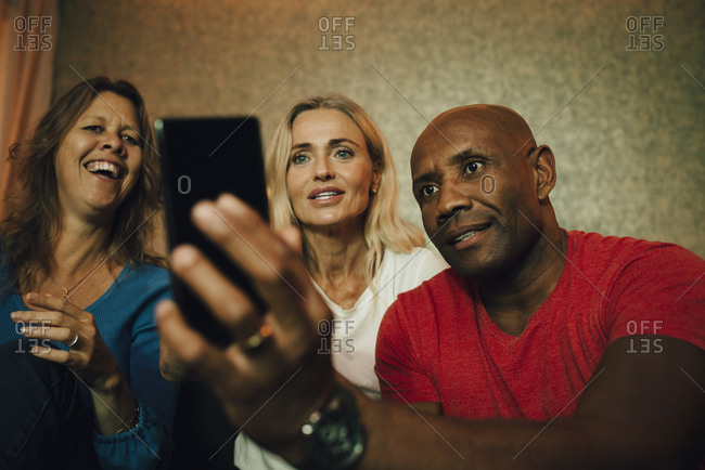 Smiling man showing smart phone to women during sporting event
