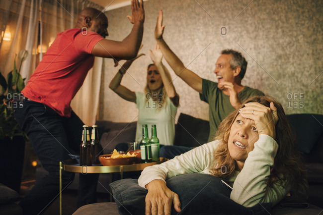 Disappointed woman sitting on sofa while friends cheering in background during sporting event