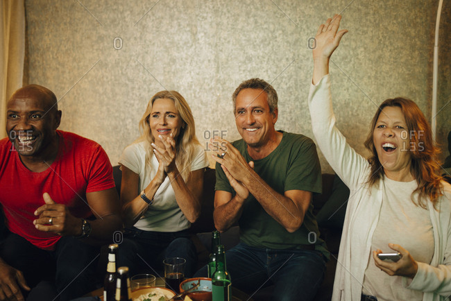 Cheerful woman with hand raised enjoying match with friends at night
