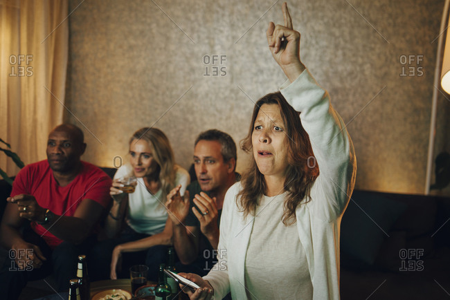 Woman with hand raised enjoying match with friends at night
