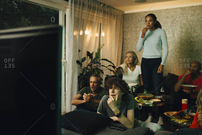 Male teenager with family by sofa watching TV during sporting event at night