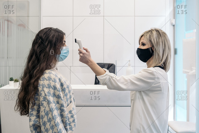 Dental clinic worker using thermometer gun to check body temperature for symptoms of viruses.
