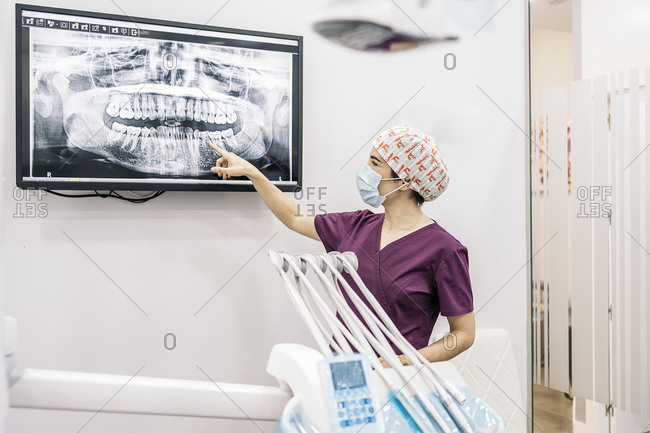 Female dentist showing her young patient a x-ray.