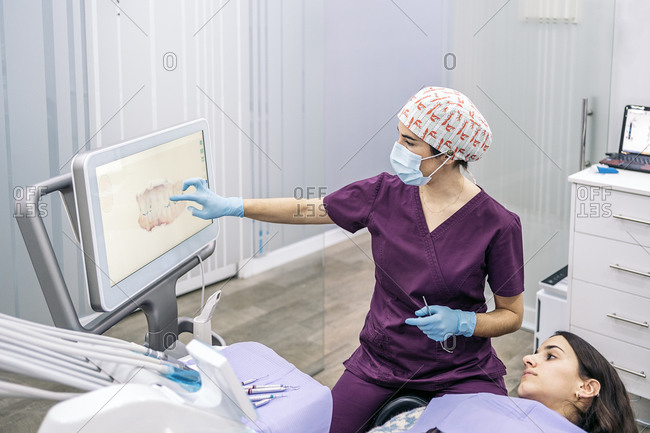Female worker of dental clinic showing an x-ray to a patient.