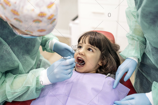 Unrecognized professional dental workers doing checkup to a little girl.