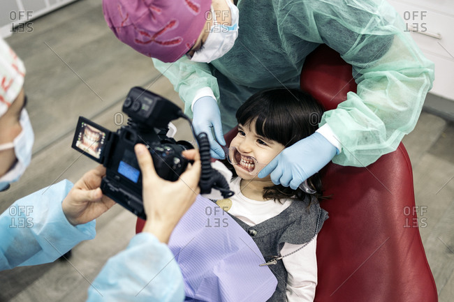 Female dentist wearing face mask taking picture of a young patient.