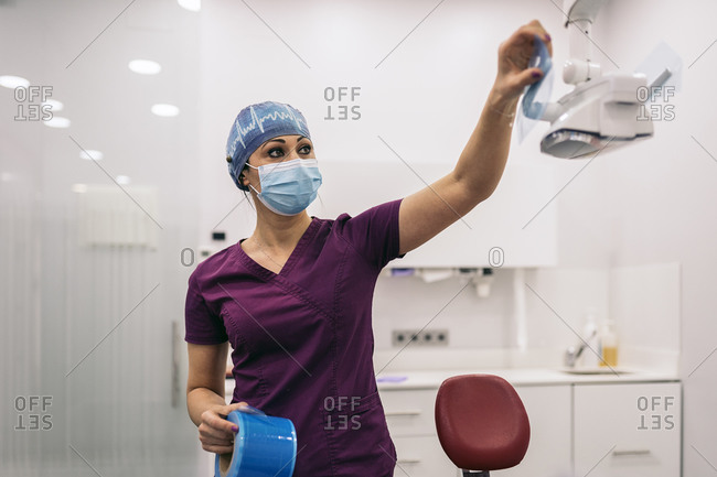 Female dentist working in modern dental clinic and wearing face mask.