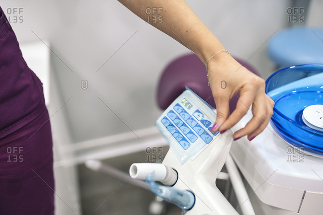 Unrecognized worker in dental clinic using water dispenser.