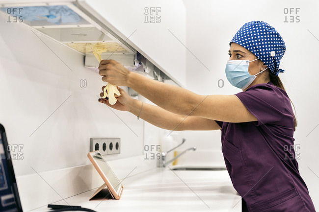Woman wearing face mask and hair net working in modern dental clinic.